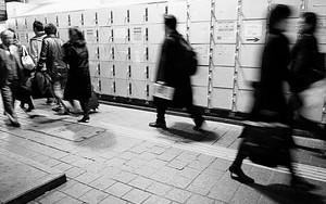 Pedestrians Walking In Front Of Lockers