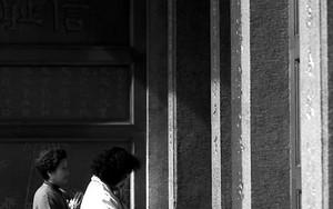 扉の外に立つ女性