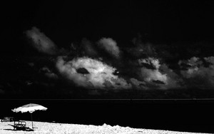 黒い空と誰もいないビーチパラソル