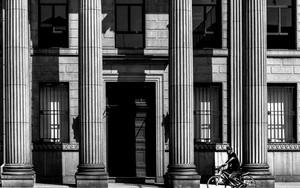 コリント様式の柱の前を通り過ぎる自転車