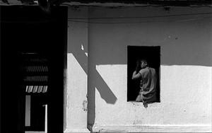 窓辺に腰掛けている若い僧侶