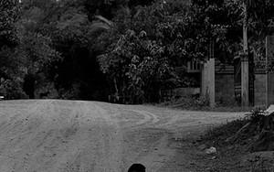 少年が砂利道に座っていた