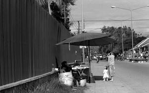 屋台の前に立つお母さんと赤ん坊