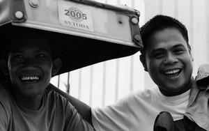 トライシクルの横にふたりの陽気な男たち