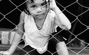 Girl Stares At The Other Side Of The Wire Netting