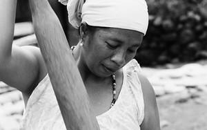 木の棒で脱穀する女性