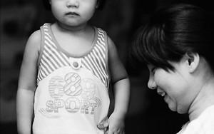 Girl Standing Beside Her Mother