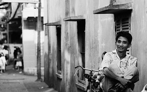 バイクの上で足を抱える男