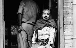 Older Woman Sat At The Door