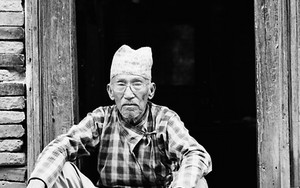 戸口に坐るダッカ・トピを被った老人