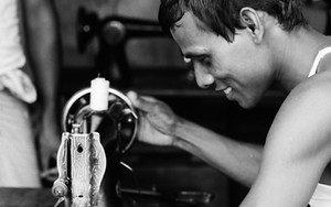 Man Manipulates A Sewing Machine With Smile
