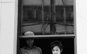 窓辺に立つふたりの青年