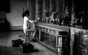 祭壇の前に腰掛ける女性