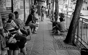 People Relaxing On The Sidewalk
