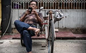 自転車タクシーの運転手とスマートフォン