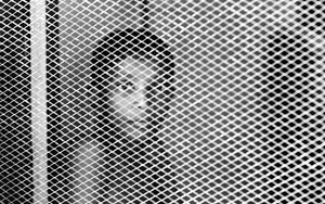 Boy In The Other Side Of A Screen Window