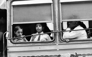 バスの窓辺に立つ子