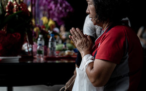 Woman Praying With A Plastic Bag