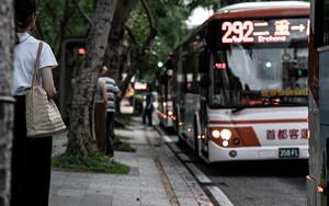 バス停でバスを待つ若い女性