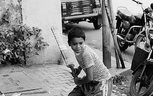Boy Holding A Bat On The Sidewalk