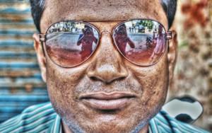 男のサングラスに映る人影