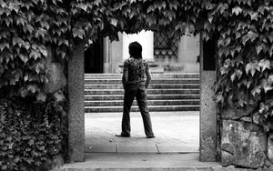 蔦絡む入り口に立つ若い男