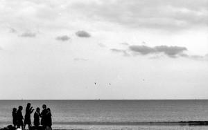 浜辺に立つ女子高生のシルエット