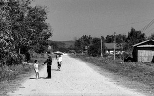 Two Kids And An Umbrella In The Unpaved Road