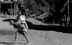 ボールで遊ぶ裸足の少年