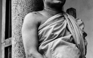 Monk Leaning Against A Pillar