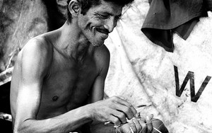 Smiling Man Repairing The Fishnet