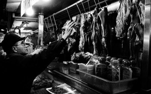 Elderly Man Extending His Arm In A Butcher