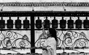 Woman Turning Around Prayer Wheels