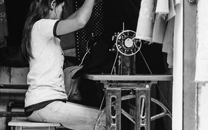 Woman Sitting In Front Of A Sewing Machine