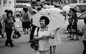 Smiling Woman Putting An Umbrella Up