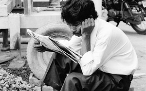 Shoeless Man Reading A Newspaper