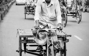 荷台付きの三輪車を漕ぐ男