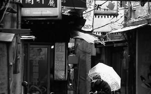 路地に立つ傘を持った男