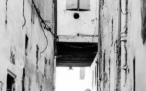 建物と建物の間を歩く女性