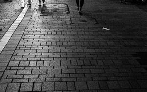 Pedestrians In The Dark Street