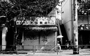 シャッターの閉まった店先の日傘