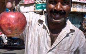 Man Pinching The Stem Of An Apple