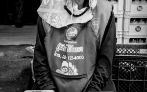 パック詰めの魚を売る女