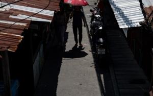 トタン屋根の間に赤い傘
