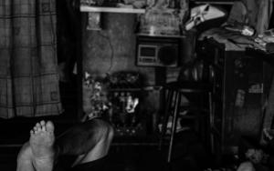 板張りの床で寝る男